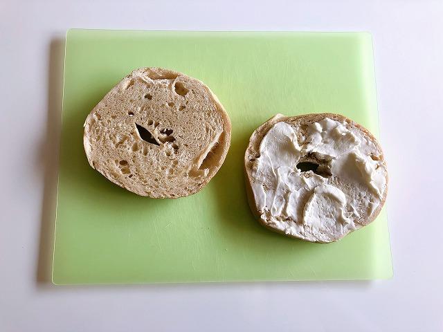 カルディベーグルにクリームチーズを塗る様子