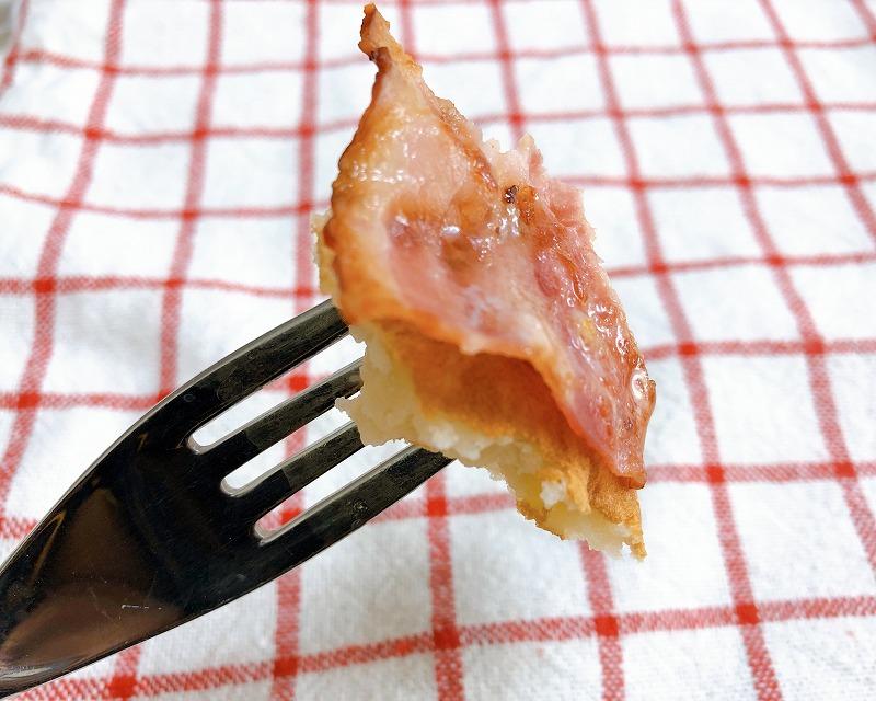 ベーコンとパンケーキを一緒にフォークで刺している写真