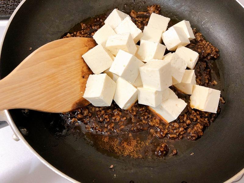 カルディ黒麻婆の素の入ったフライパンに豆腐を入れた様子