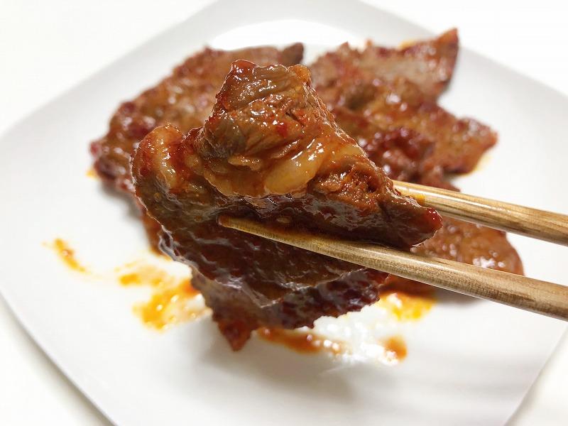 焼きあがった牛肉を箸でつかんでいる様子を撮影した写真