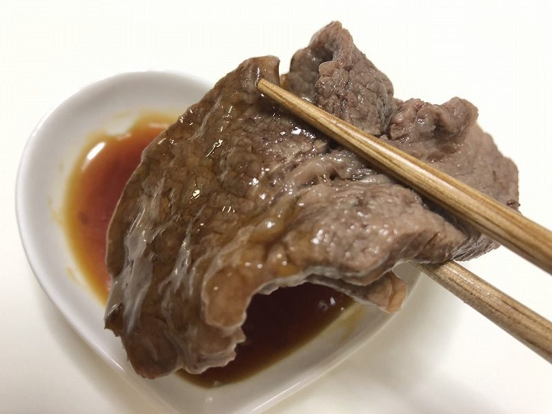 焼きあがった牛肉を箸でつかみ、タレを付けている様子を撮影した写真