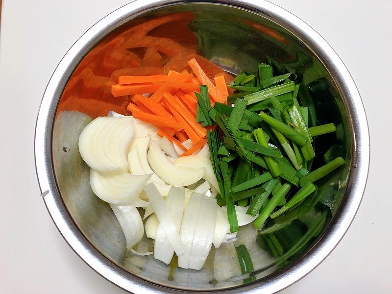 「プルコギの素」を使って牛肉を調理するのに必要なニンジン、玉ねぎ、ニラを切った写真