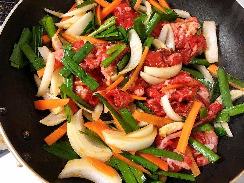 混ぜておいた牛肉、野菜、「プルコギの素」を油を引いたフライパンで中火で炒めている様子