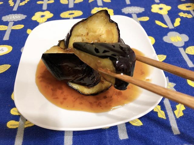 完成したナスの素揚げ甘酢だれを箸で持ち上げている様子を撮影した写真