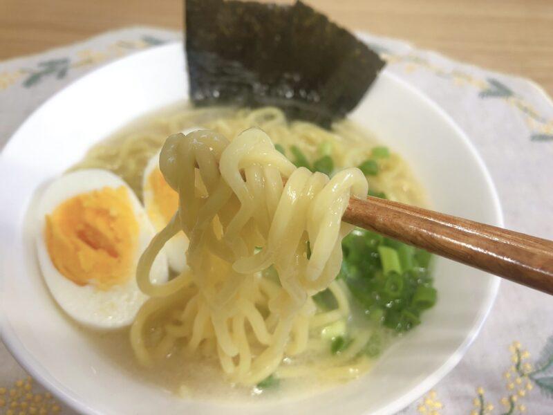 コムタンスープのラーメンを箸で持ち上げている様子